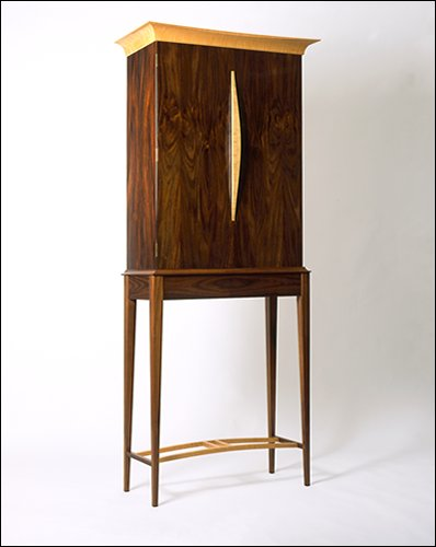 This contemporary cabinet on a stand, finished with French polish throughout, is made from Indian Rosewood, ripple Maple and Cedar